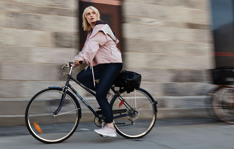 Women riding a bike wearing Hyba clothing by Reitmans
